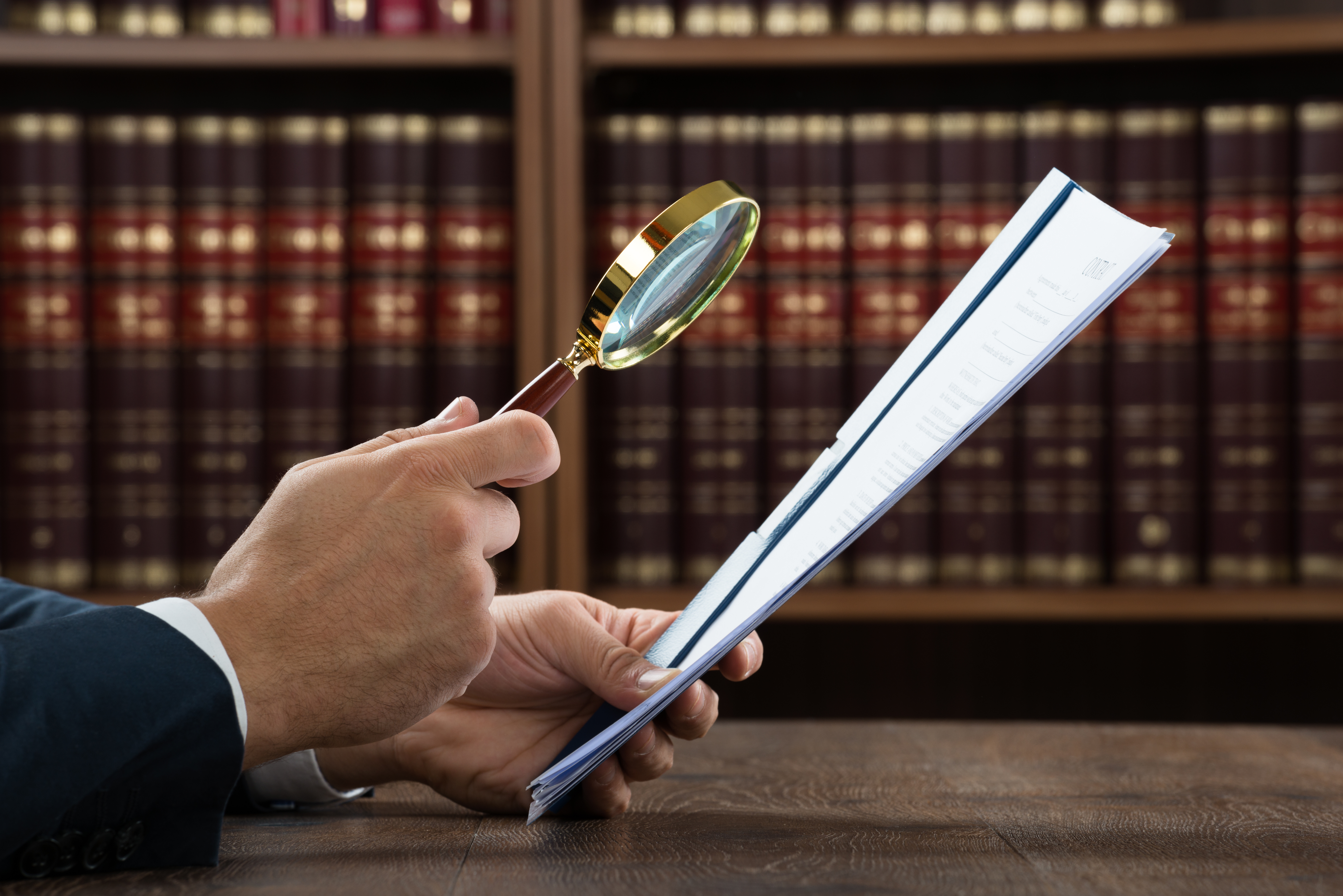 Mann mit Lupe sichtet das Vertrag Rechtliche Prüfung Unlauterer Wettbewerb