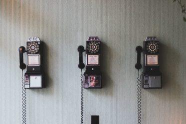 Kontakte und Anmeldungen, Bild von 3 alten Telefonen an der Wand als Sinnbild für Kontakte
